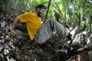 Glor attempts to use old man strength to dislodge a stone while searching for dwarf geckos.